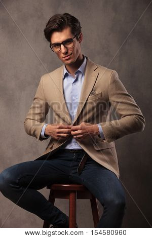 smiling business man sitting and unbuttoning his coat, studio picture