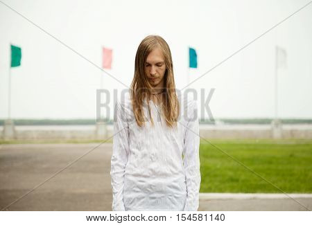 Young white man standing at the park with sad face and closed eyes. Peaceful tranquil scene with a person meditating outdoors