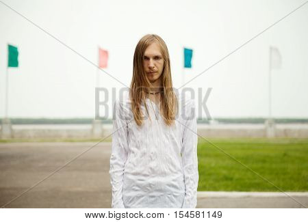 Young blond man with long hair and serious face staring at you. Peaceful tranquil scene with a person standing at the park