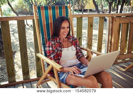 Mid shot of the Caucasian tanned woman who is using a laptop when sitting on a summer beach chair. Checking her e-mail, answering the messages during the vacation. Summer holidays.