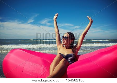 A shot of a young smiling lady sitting and rejoicing on a pink air rubber boat holding her hands up and showing her palms to the sun.