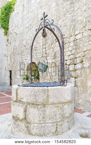 The interior of the Frankopan Castle at Kamplin square in Krk Croatia - Frankopanski Kastel part of the medieval city walls. View of the well stern with a soldier helmet as a bucket
