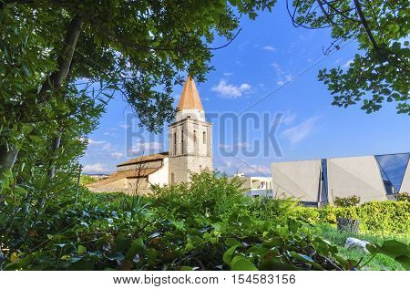 The pyramidal tower of the Church of our Lady of Health a romanesque cathedral formerly named St Michael the archangel basilica at the Square of the The Glagolitic housed monasteries on Krk island in Croatia and the elementary school mirrors.