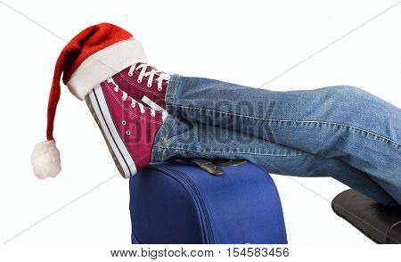 young boy with his legs over the suitcase waiting on white background with santa hat on the feet