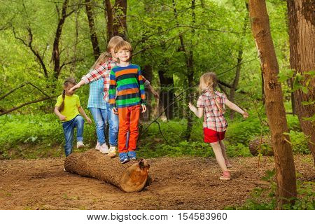 Portrait of Cute little boys and girls walking on trunk of tree in summer park