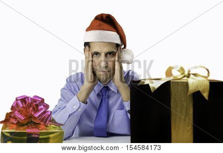 Stressed man shopping gifts for christmas wearing red santa hat looking angry and distressed