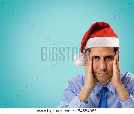 portrait of stressed man wearing red santa hat looking angry and distressed with copyspace on blue background