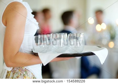 Waitress Holding A Dish Of Glasses