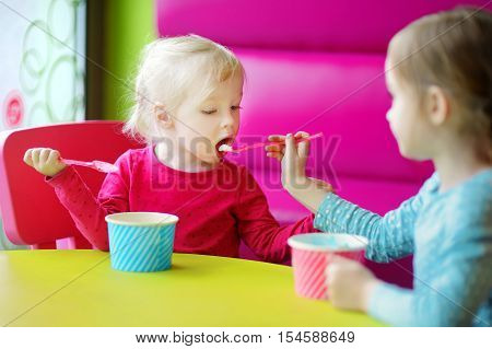 Two Cute Little Sisters Eating Ice Cream Together