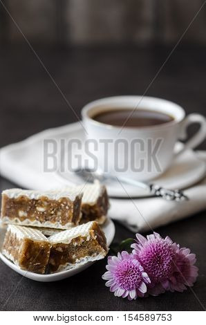 Closeup of wafers puff cakes with caramel and a cup of coffee