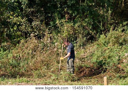 Wroxham Norfolk United Kingdom - October 25 2016: Man undertaking conservation work alongside River Yare