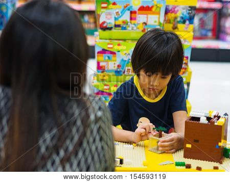Hat Yai, Songkhla, Thailand - October 3, 2016 : Mother is looking at Child plays lego blocks at Lego shop in CentralFestival Hat Yai