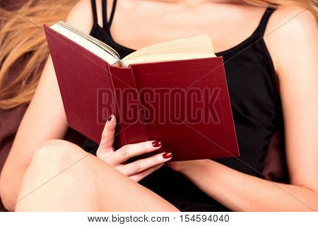 close up of young woman reading book in bed