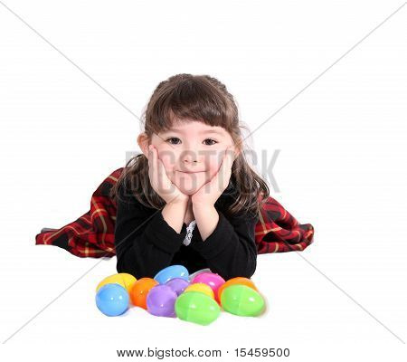 adorable little girl laying with Easter eggs isolated on white