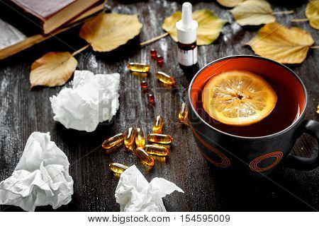 concept cold - treatment with hot tea and medecine on wooden background