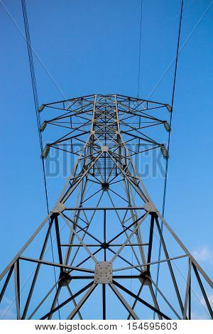 High voltage 110kV reliance power line tower front-bottom view on blue sky