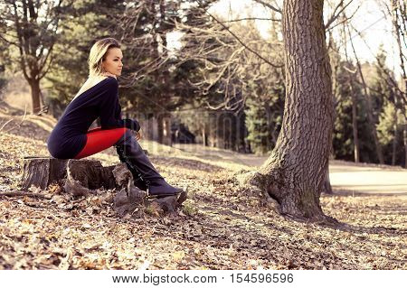 Young Beautiful Woman Is Sitting On A Stump In The Forest