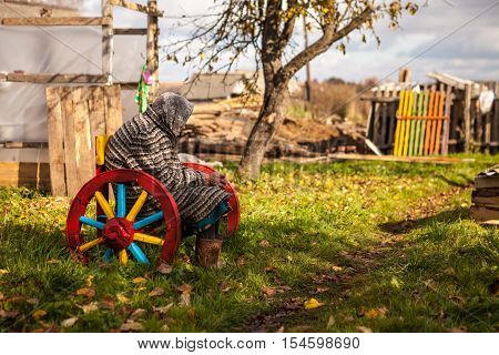 Portraiture of an old woman senior sitting on a wooden bench with colorful old wagon wheel in garden in country backyard on sunny day