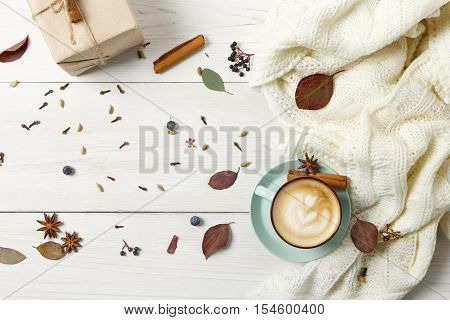 Autumn cappuccino composition. Blue coffee cup top view with foam, cloves, cinnamon, present box and warm sweater at white wood background. Fall hot drinks concept