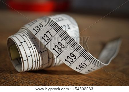 White tape measure (tape measuring length in meters and centimeters) on the wooden surface as symbol of tool used by tailor and people reducing weight during diet