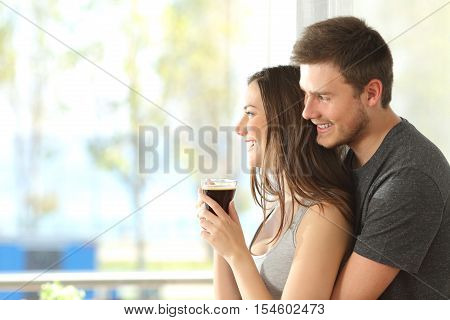 Happy couple or marriage hugging and looking through the window of an hotel or home