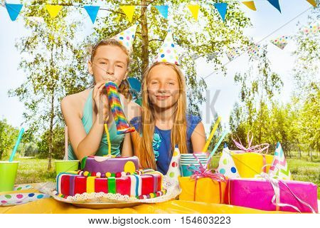 Portrait of two happy young girls playing with party blowers, standing next to the birthday cake, at the outdoor birthday party
