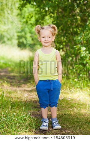 Full-length portrait of cute little girl, standing with hands in pockets on the path in the green park