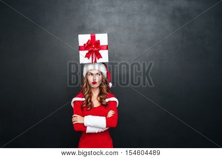 Upset sad woman in red santa claus outfit with present box on her head standing with arms folded isolated on a black background