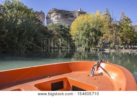 Alcala del Jucar Spain - October 29 2016: Jucar river boat of recreation in small lagoon in the central part of the town at the top of mountain limestone is situated castle of Almohad origin of the century XII take in Alcala of the Jucar Albacete province