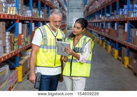 Warehouse workers discussing with digital tablet in the warehouse