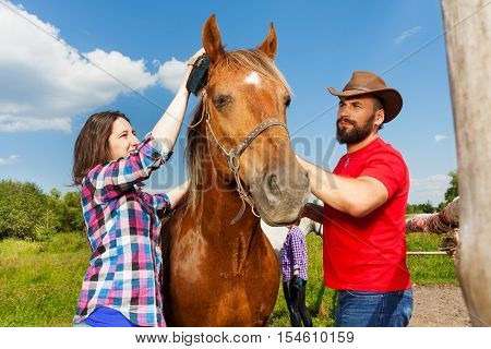 Happy young couple, man in cowboy hat and pretty woman, brushing the mane of their purebred bay horse