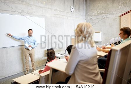 education, high school, university, teaching and people concept - group of students and teacher with marker standing at white board at lecture