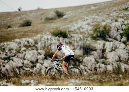 racer mountainbiker in sports bike rides on a mountain trail. competitions in cross-country bike