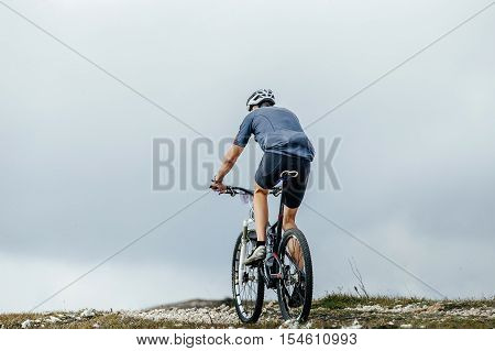 rear view male rider on a sports bike. race mountainbike in mountains