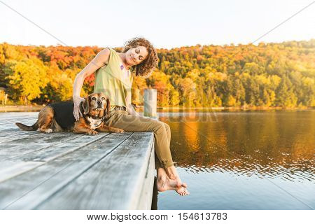 Woman And Dog Relaxing On The Dock