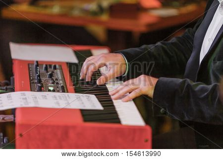 Hands and synthesizer. Part of the body. Hands on the white keys of the synthesizer playing a melody. Men's hands on the musical keyboard, playing the notes melody. Music on the piano.