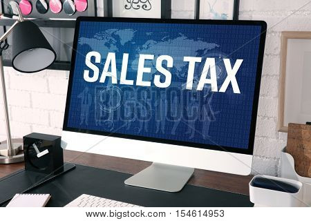 Modern workplace with computer. Text SALES TAX on screen. Online tax report concept.