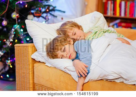 Two little blond sibling boys sleeping in bed near Christmas tree with lights and illumination. Tired kids, children dreaming and relaxing. Happy family of two brothers.