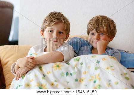 Two little kid boys watching tv at home. Preschool children enjoying cartoons on television. Sitting together on couch. people, children, television, friends and friendship concept