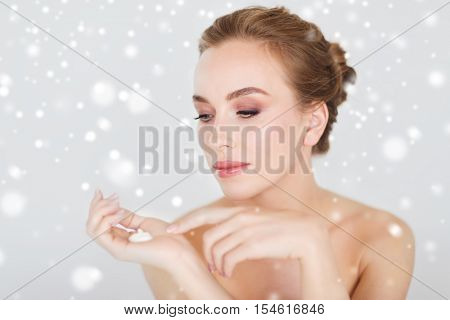beauty, people, skincare, winter and cosmetics concept - happy young woman with moisturizing cream on hand over gray background and snow