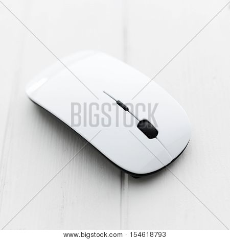 White computer wireless mouse with pad on a wooden background
