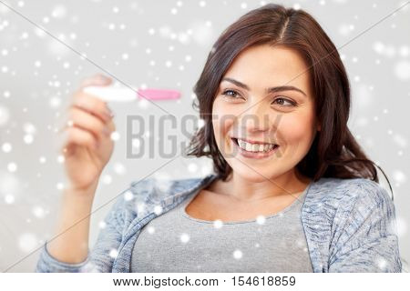 fertility, winter, maternity and people concept - happy smiling woman looking at pregnancy test at home over snow