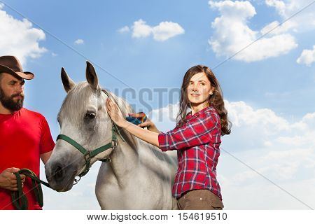 Portrait of pretty young woman brushing beautiful white horse while man in cowboy hat holding it by a bridle