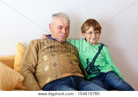 Little kid boy and grandfather watching tv at home. Preschool child and senior man enjoying cartoons on television. Sitting together on couch. people, children, television, friends and friendship concept