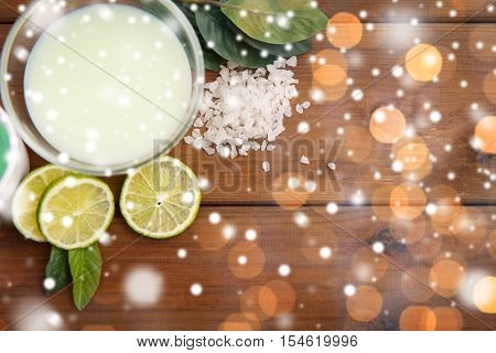 beauty, spa, bodycare, natural cosmetics and wellness concept - citrus body lotion in glass bowl and sea salt with limes on wooden table over lights and snow