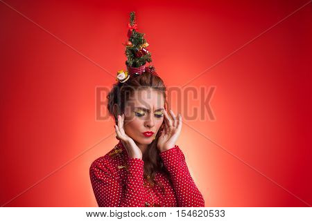 New Year's and Christmas efforts and preparations. Girl with New Year tree instead of santa hat on head had headache about winter holidays celebration. Woman arranging decorations of Xmas tree. Creative fun studio photo.