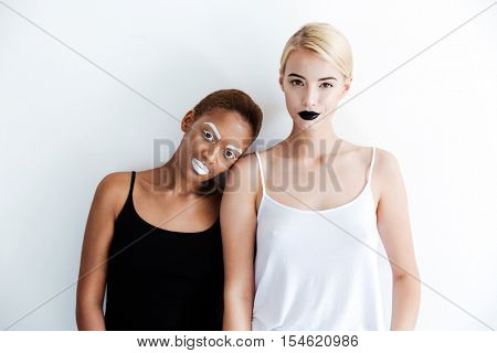 Short african and tall caucasian young women with creative makeup over white background