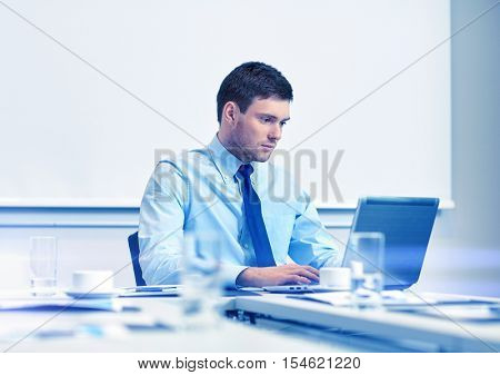 business, people and work concept - businessman with laptop computer sitting in office in front of whiteboard