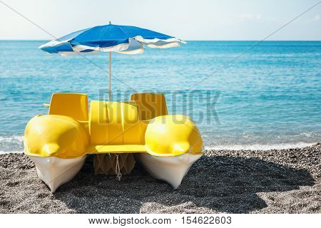 the yellow catamaran is on the beach. Rent a catamaran for tourists, swimming in the sea