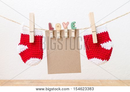 Blank paper with baby socks hanging on love clothesline. Christmas concept.